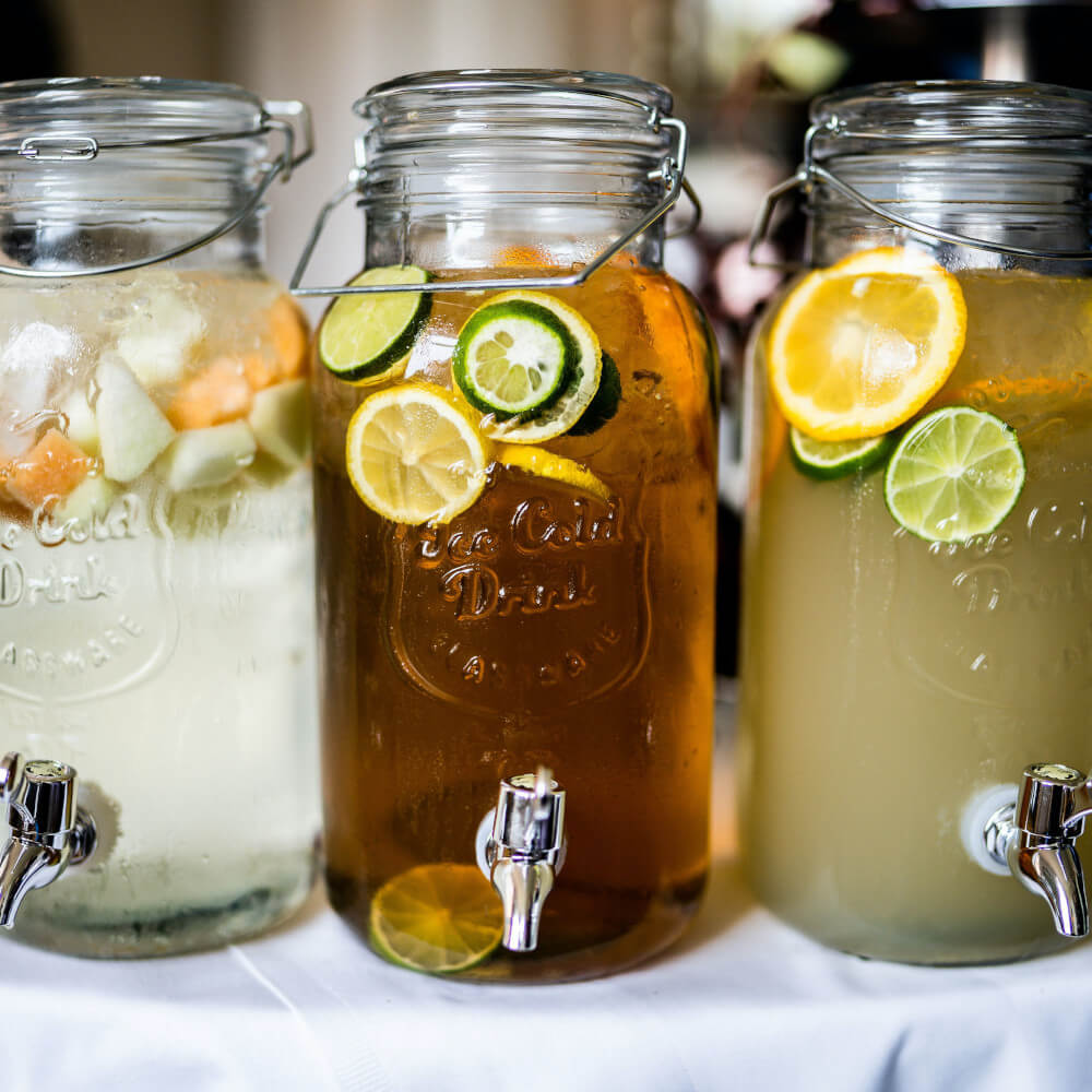 Firefly Peach Punch: 3 glass jars with spigots filled with punch and fruit slices