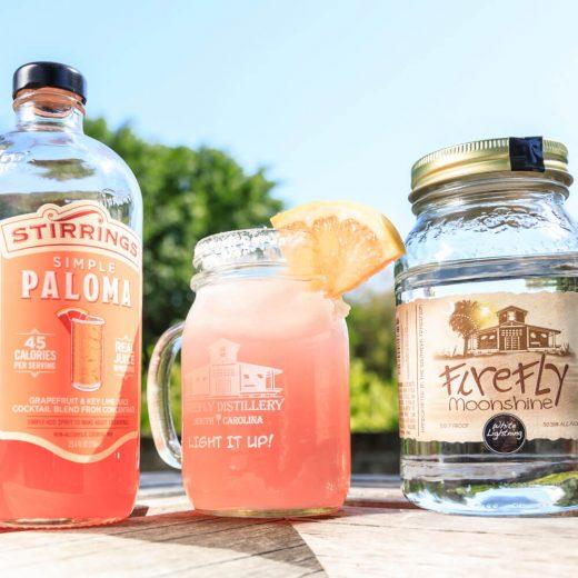 Paradise Paloma: 2 bottles and a mason jar with pink liquid and grapefruit slice garnish