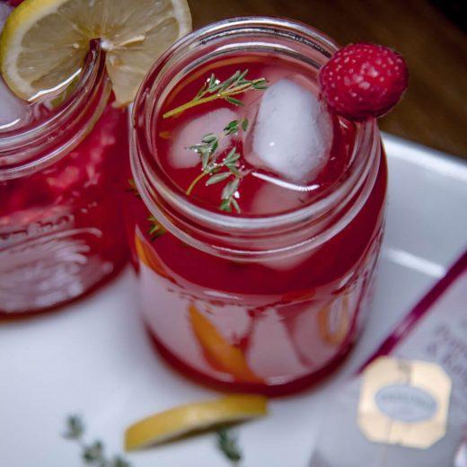 Mason jar with ice and cocktail, raspberry garnish